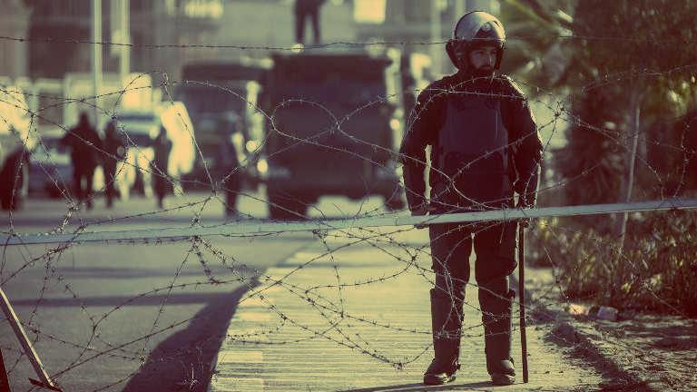 فرد شرطة خلف جدار حاجز